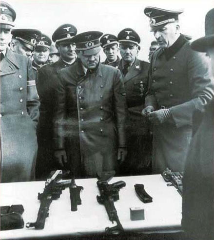 Hitler looking at weapons including an StG-44